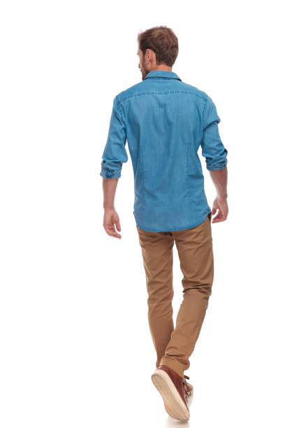 back view of  casual man walking and looking to side back view of a casual young man walking and looking to side on white background walking stock pictures, royalty-free photos & images