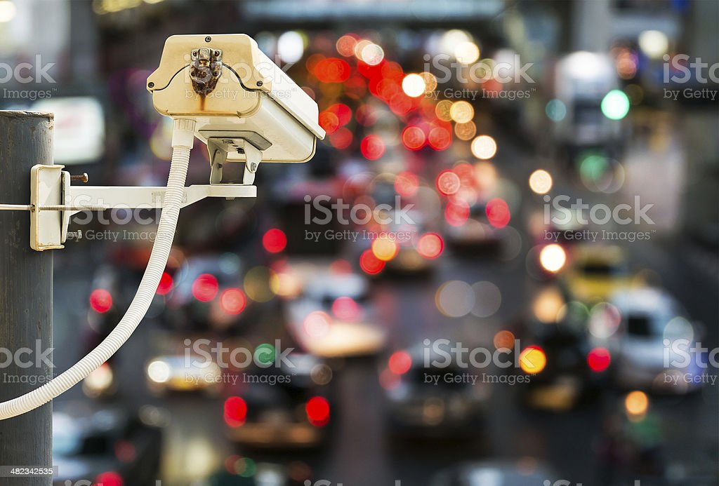 Back view of CCTV Camera with traffic jam light bokeh stock photo