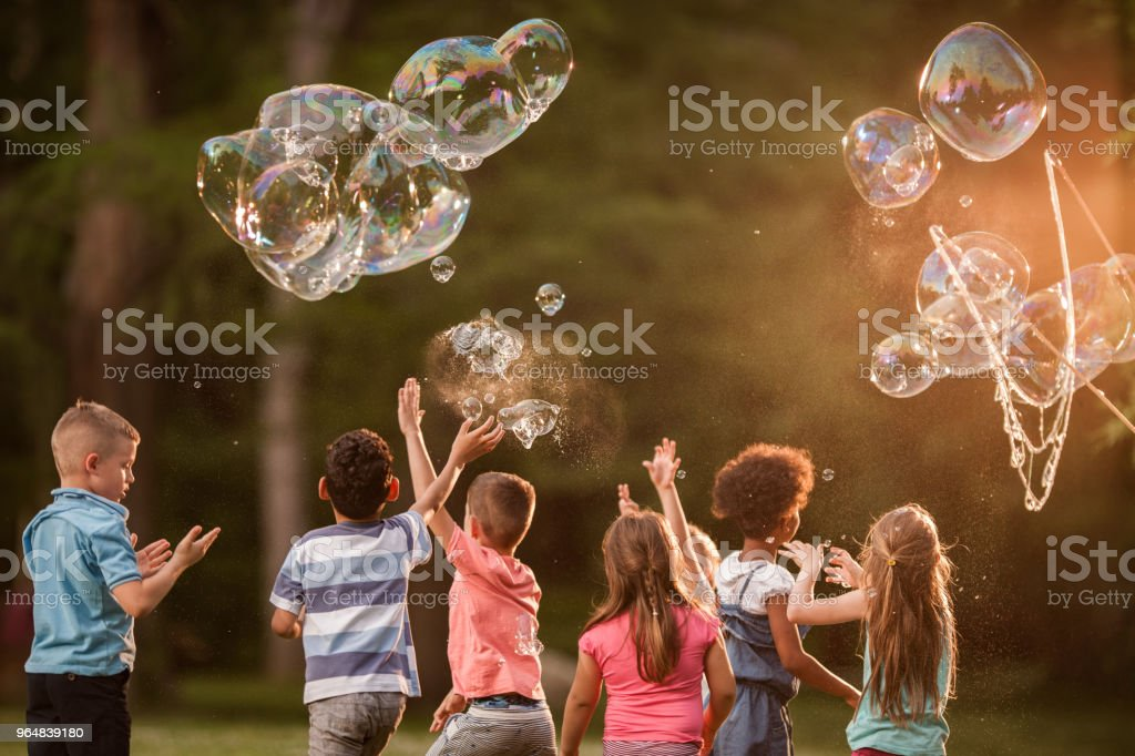 Back view of children playing with rainbow bubbles in nature. royalty-free stock photo