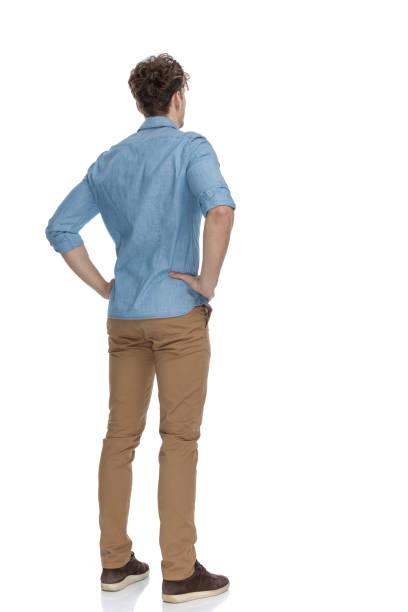 widok z tyłu zainteresowanych przypadkowy facet trzymający się za ręce na biodrach - plecy zdjęcia i obrazy z banku zdjęć