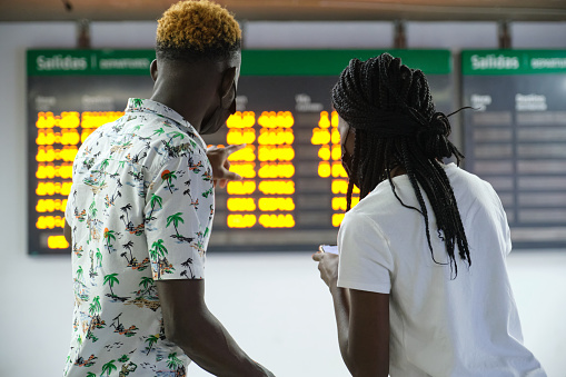Back view of couple in a train station wearing protective face masks, looking at their smartphone and the travel board with train schedule information.
