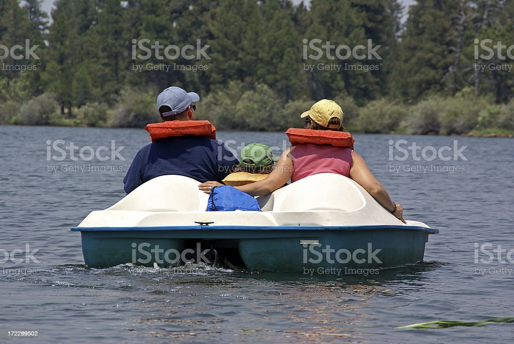 Back view of couple in paddle boat on the lake stock photo
