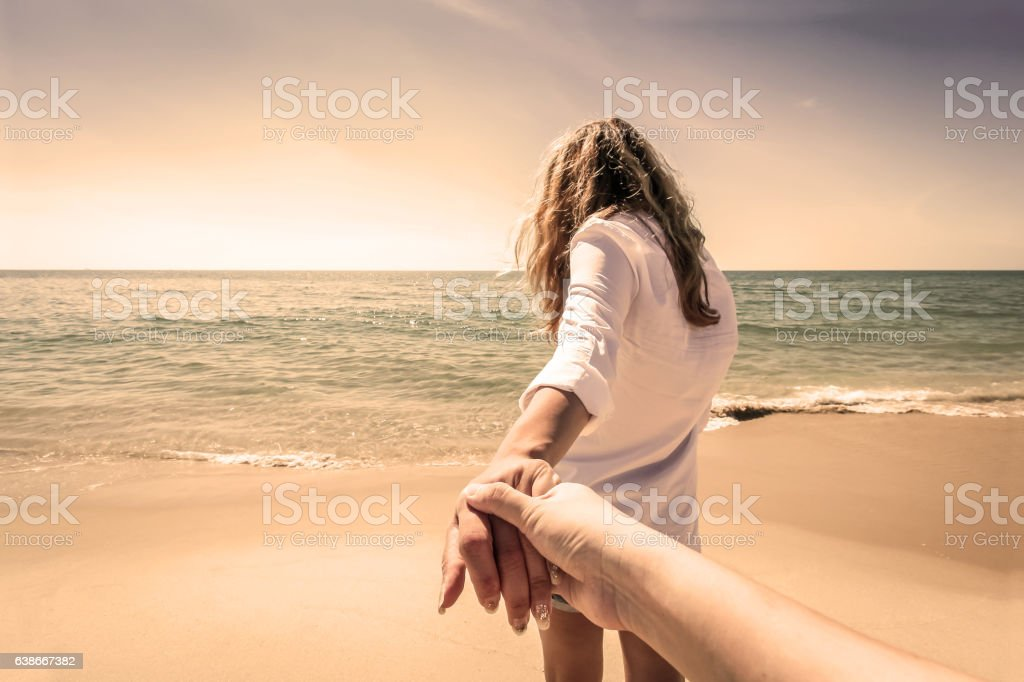 Back view of couple walk holding hands on a beach stock photo