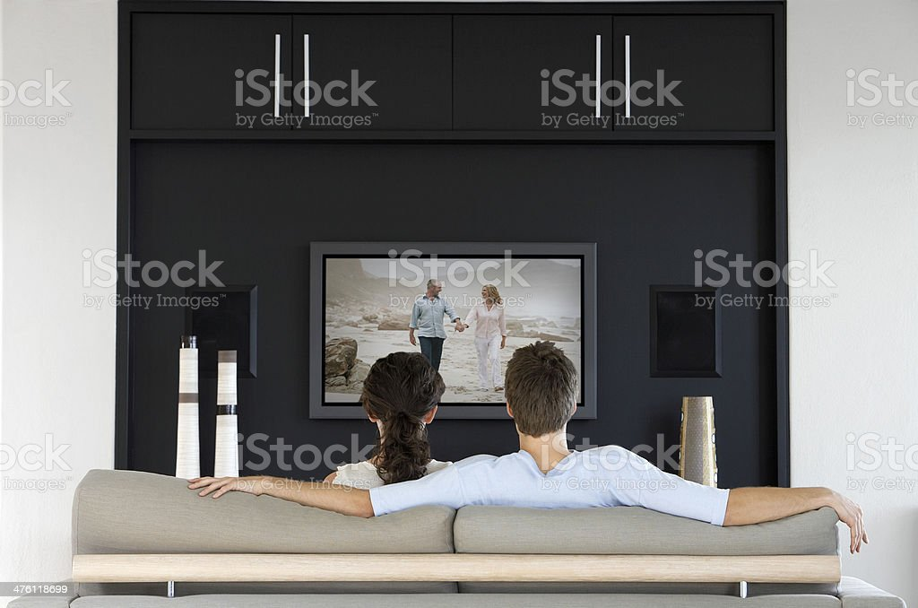 Back view of couple watching movie television in living room stock photo
