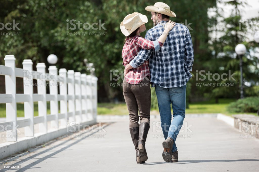 back view of cowboy with his girlfriend walking on pathway in park at daytime stock photo