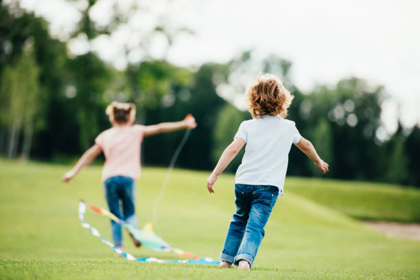 back view of cute little boy and girl playing with lite in park stock photo