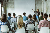 istock Back view of design professionals having training class in the office. 1199194222