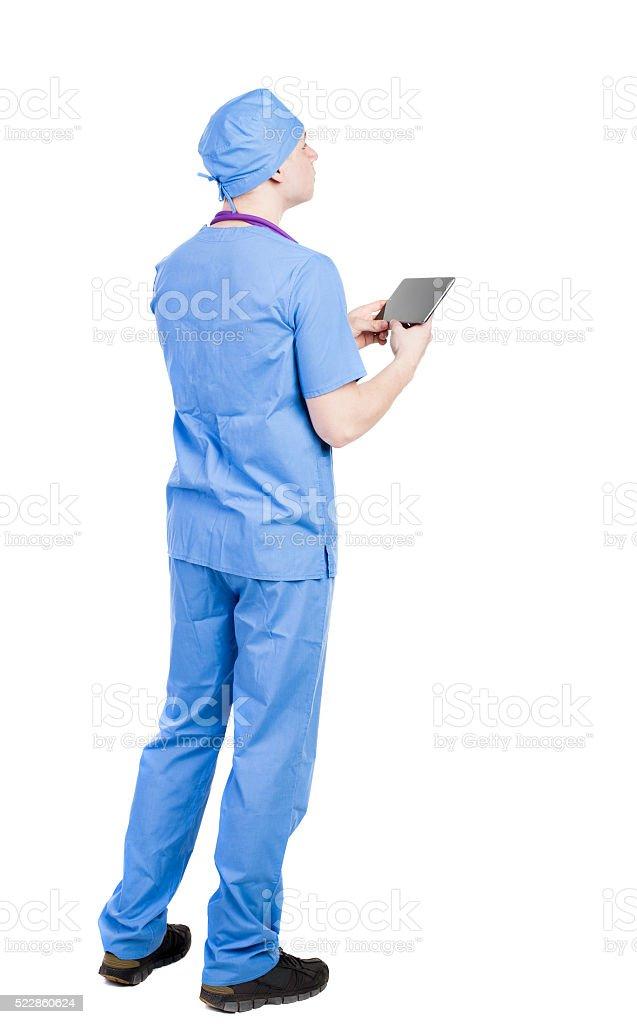 Atrás vista de médico retención de computadora de tableta en la bata de baño - foto de stock