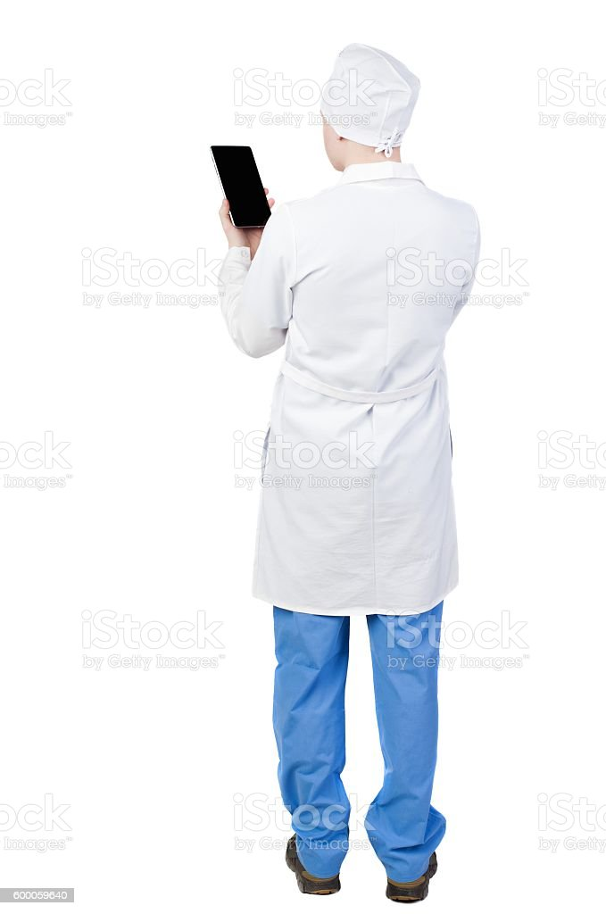 Back view of doctor in robe holding tablet computer. stock photo