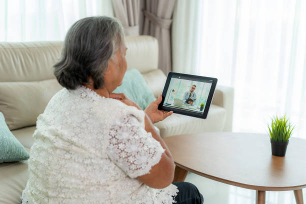 vista posterior de la anciana haciendo videollamada con su médico con su sensación de dolor de garganta en la tableta digital en línea consulta de tecnología digital de salud mientras se queda en casa. - telehealth fotografías e imágenes de stock