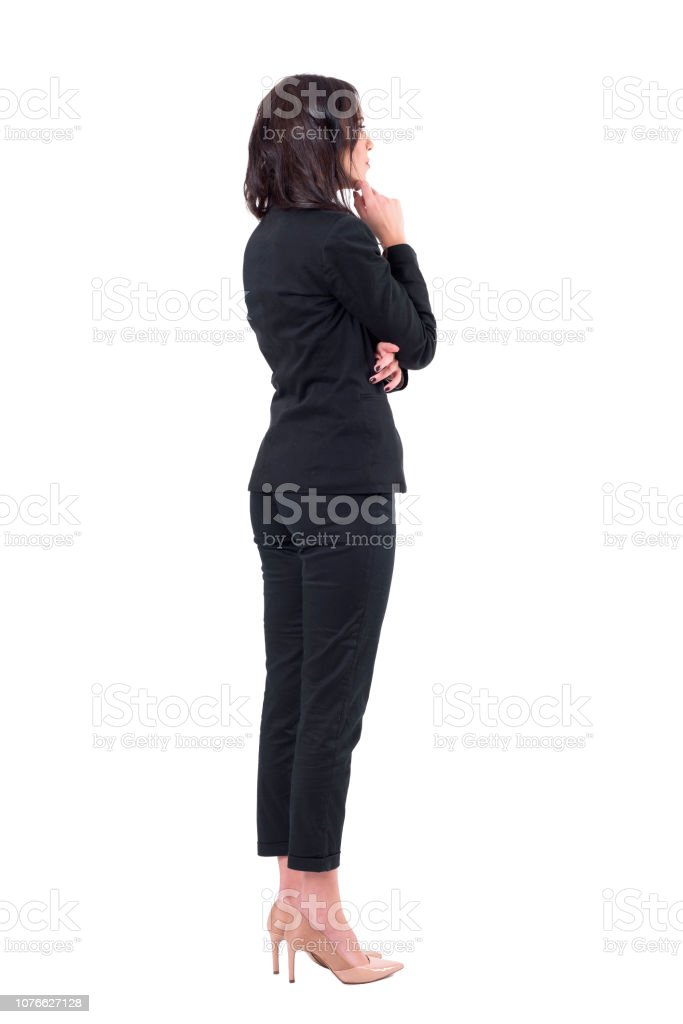 Back view of elegant business woman in suit looking away at something watching interested foto stock royalty-free