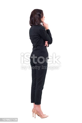 Back view of elegant business woman in suit looking away at something watching interested. Full body isolated on white background.