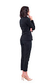 istock Back view of elegant business woman in suit looking away at something watching interested 1076627128