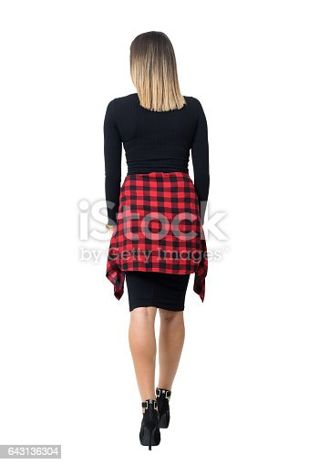 Back view of elegant young woman in black dress and stiletto shoes walking away. Full body length isolated over white studio background.