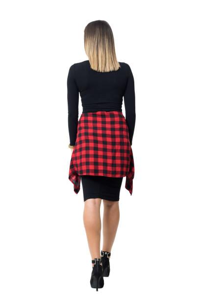 Back view of elegant woman in black dress walking away. stock photo