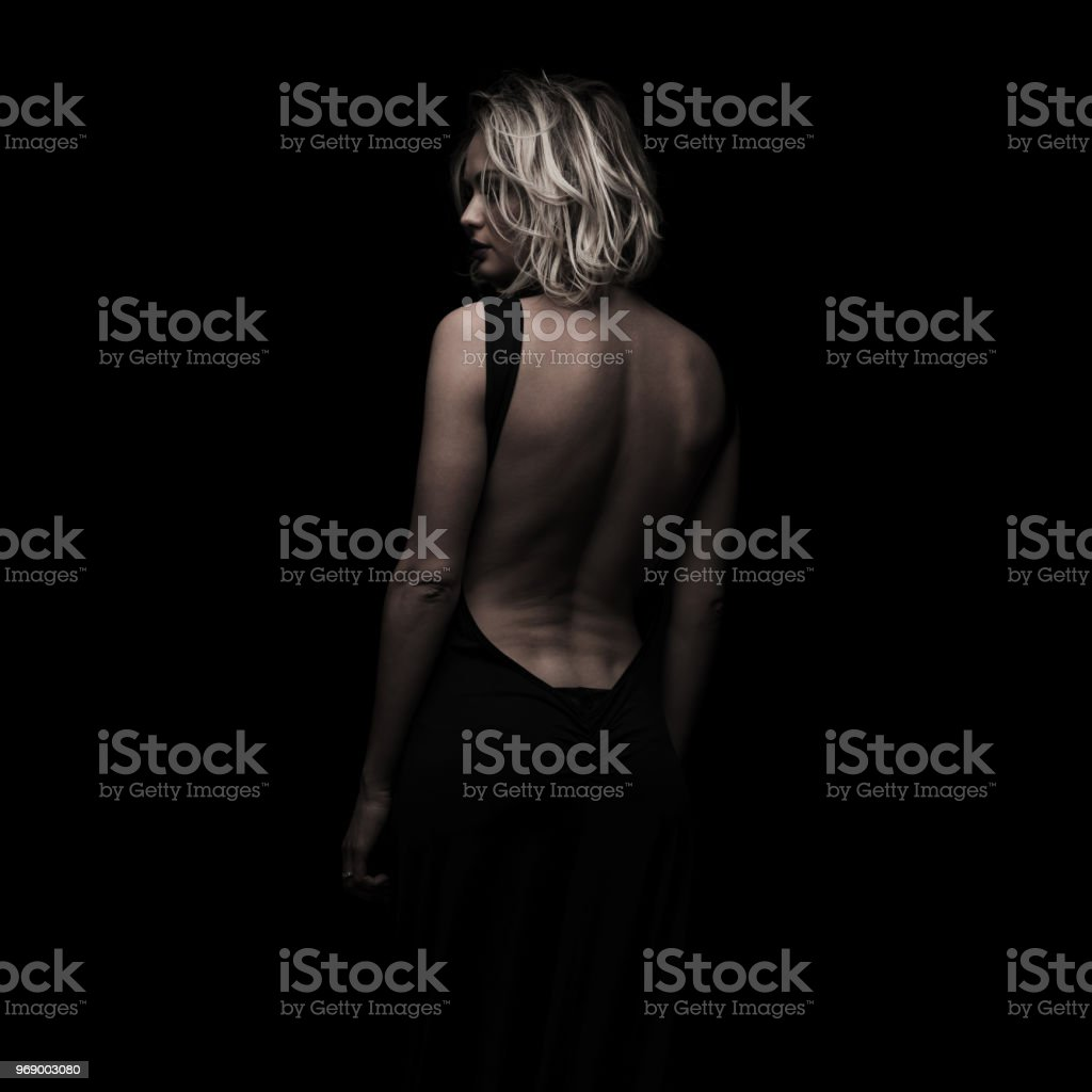 back view of elegant woman wearing a backless black dress stock photo