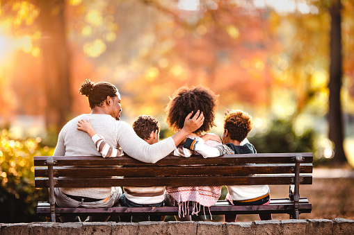 Rear view of African American family embracing while relaxing on a park bench in autumn day.