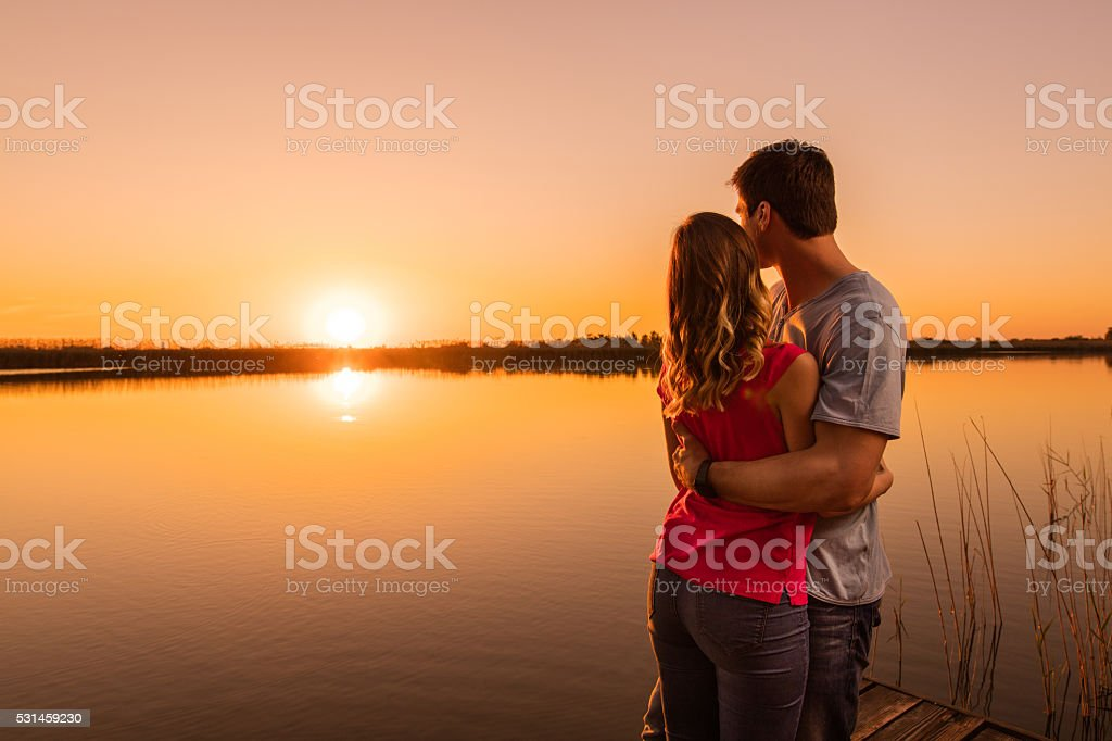 Back view of embraced couple by the lake at sunset. stock photo
