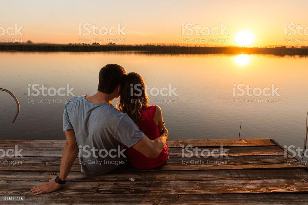 Back view of embraced couple enjoying at sunset by lake. stock photo