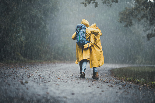Back view of embraced couple in raincoats hiking on a rain.