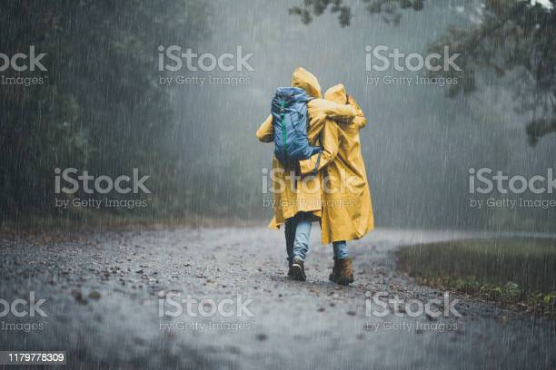 Photo of Back view of embraced couple in raincoats hiking on a rain.