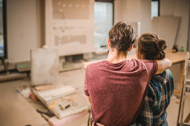 Back view of embraced couple in their renovating apartment. stock photo