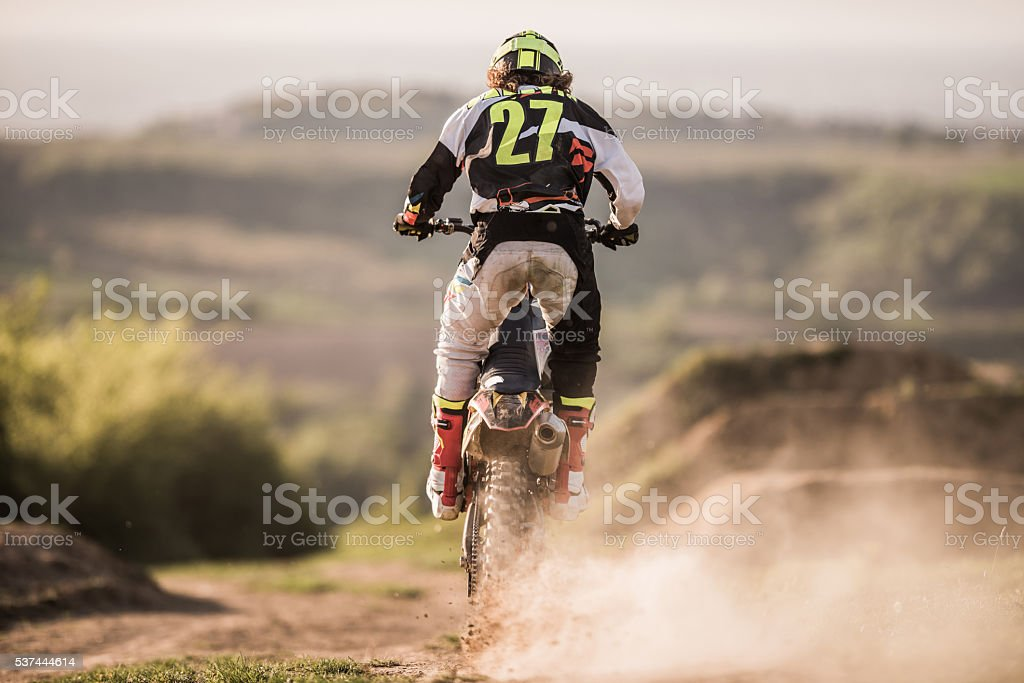 Back view of enduro motocross rider on a dirt track. stock photo