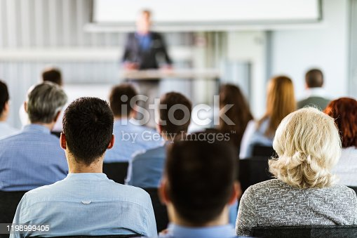 Rear view of business seminar in a board room. Focus is on blond woman and man next to her.