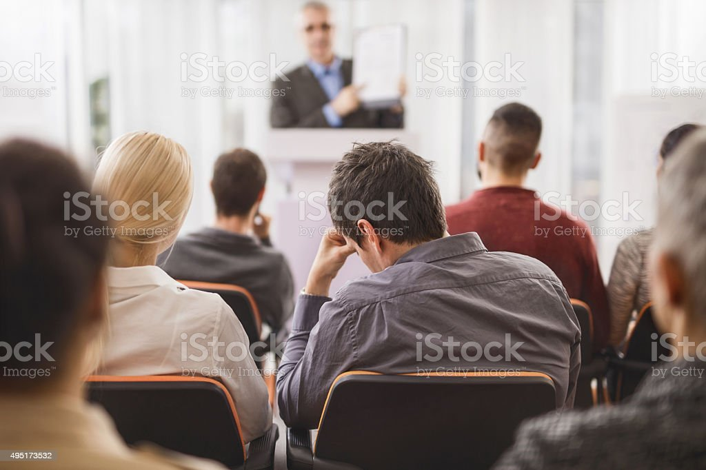 Back view of exhausted businessman attending an education event. stock photo