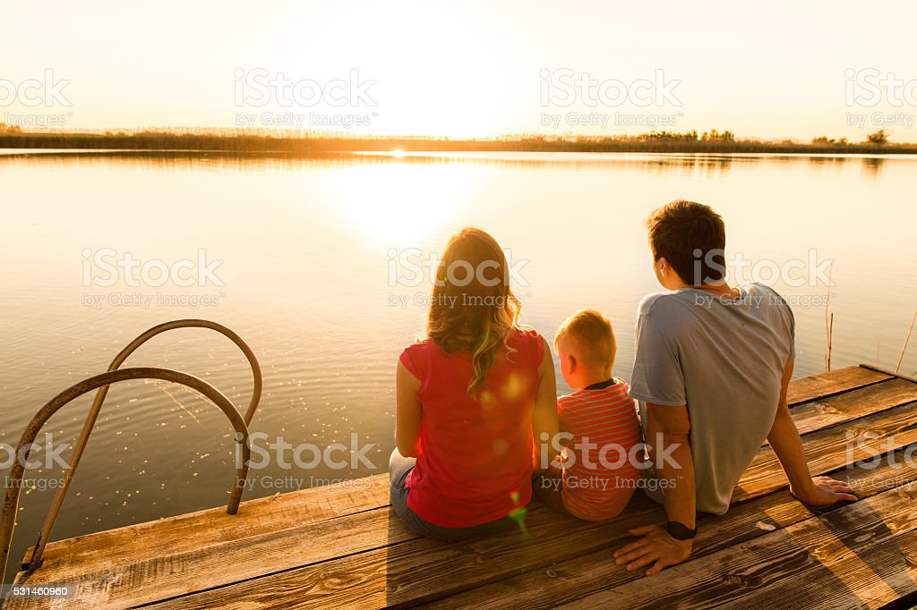 Back view of family relaxing on a pier at sunset. stock photo