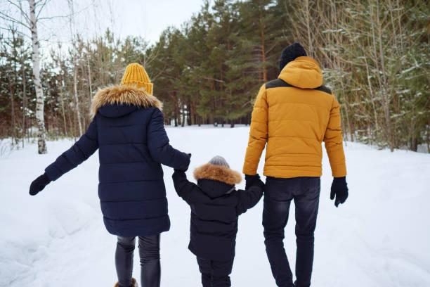 Rückansicht der Familienspaziergänge am Wintertag. – Foto