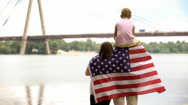 Back view of family wrapped in USA flag looking at bridge, independence day Back view of family wrapped in USA flag looking at bridge, independence day citizenship stock pictures, royalty-free photos & images
