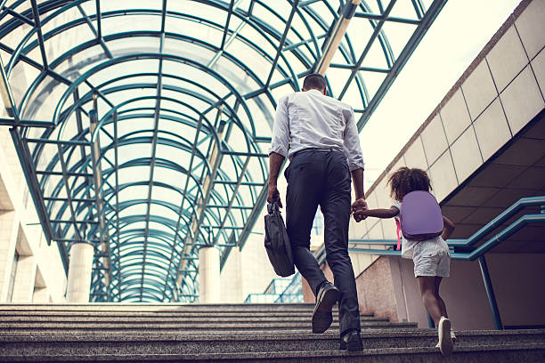 Back view of father and daughter walking up the stairs. stock photo