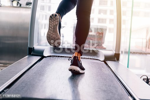 494003079istockphoto Back view of feet with sneakers of female runner / jogger running on treadmill indoors in action 1128153121