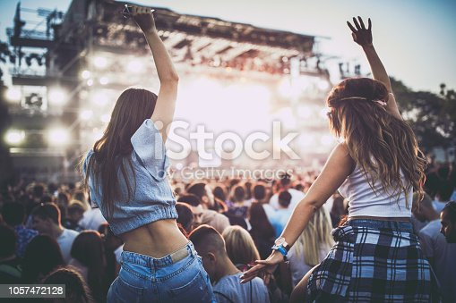 Rear view of carefree female friends dancing on a music festival.