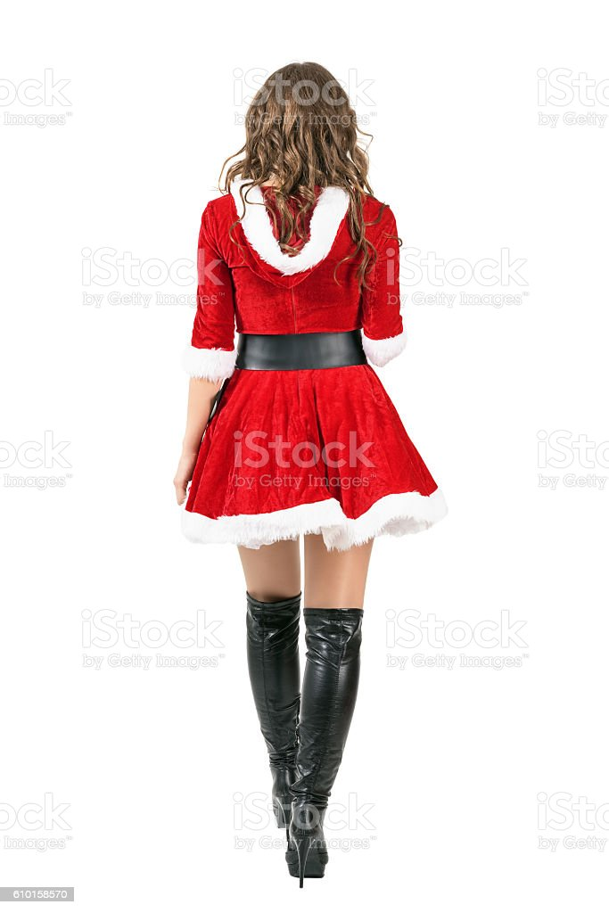 Back view of female Santa in Christmas dress walking away stock photo