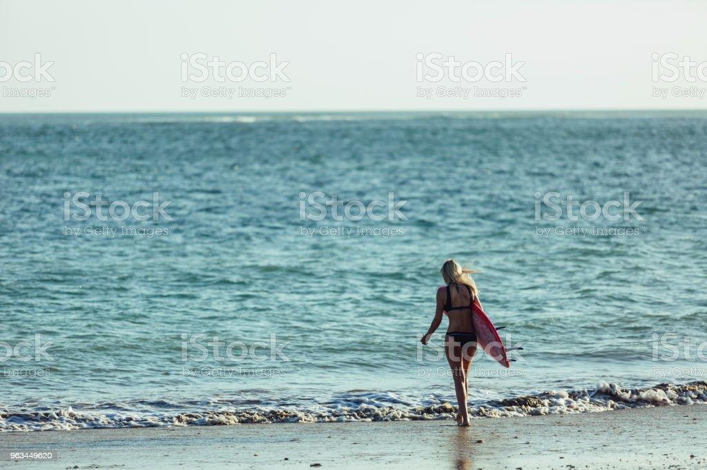 arkadan görünüşü kadın sörfçü okyanusa sahilde yürüyüş surfboard ile - Royalty-free Arka görünüm Stok görsel