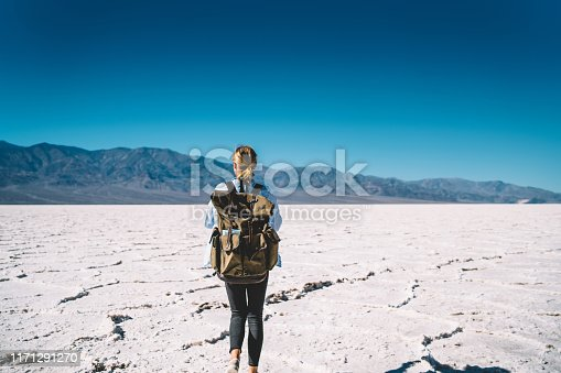 Back view of female traveler exploring death valley national park carrying equipment in rucksack for taking photo,young woman walking on touristic route in beautiful natural landscape on daytime