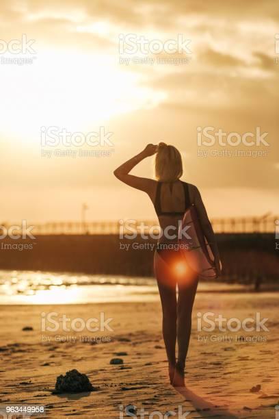Widok Z Tyłu Dziewczyny Pozującej Z Deską Surfingową Na Plaży O Zachodzie Słońca Z Tylnym Światłem - zdjęcia stockowe i więcej obrazów Deska surfingowa