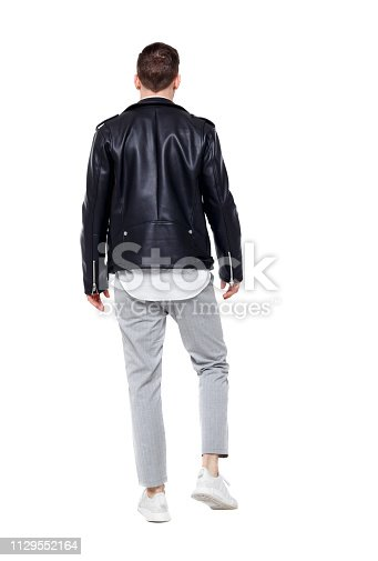 Back view of going  handsome man in a leather jacket and trousers. walking young guy . Rear view people collection.  backside view of person.  Isolated over white background. Stylish guy in the suit goes into the distance