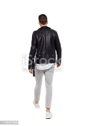 Back view of going  handsome man in a leather jacket and trousers. walking young guy . Rear view people collection.  backside view of person.  Isolated over white background. The rocker goes into the distance