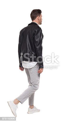 Back view of going  handsome man in a leather jacket and trousers. walking young guy . Rear view people collection.  backside view of person.  Isolated over white background. Brunette with a stylish hairstyle leaves