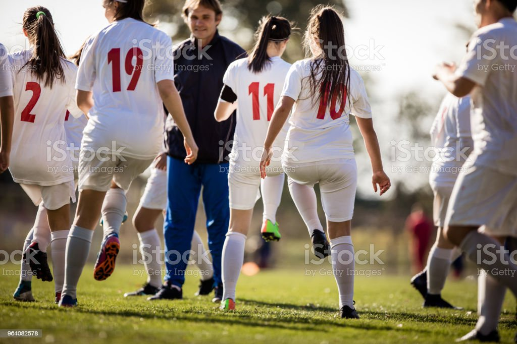 Back view of group of female soccer players warming up on a playing field. - Royalty-free Adolescence Stock Photo