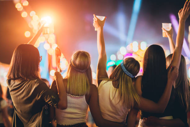 Back view of group of girls having fun at the music festival stock photo