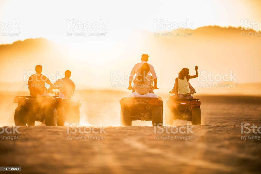 Back view of group of people driving quad bikes. stock photo