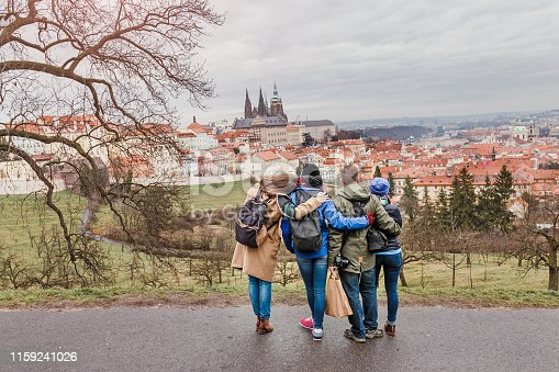 Back view of group of people hugging in Prague park at spring. Travel with friends concept