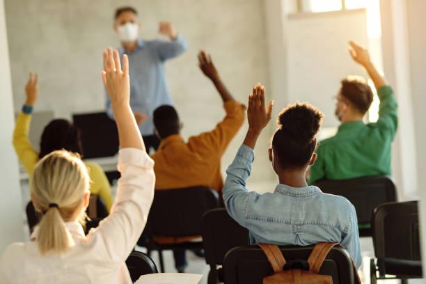 rückblick auf eine gruppe von studenten, die während eines unterrichts im hörsaal die arme heben. - erwachsene person stock-fotos und bilder