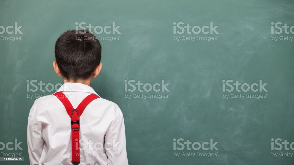 Back View Of Guilt Little Boy Standing In Front Of Green Chalkboard stock photo