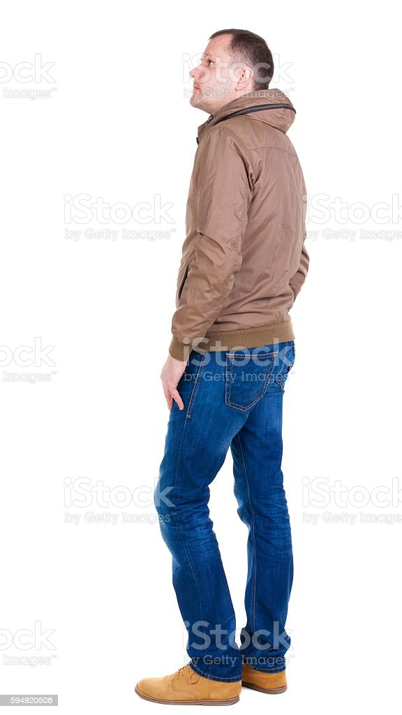 Back view of handsome man in brown windcheater looking up. stock photo