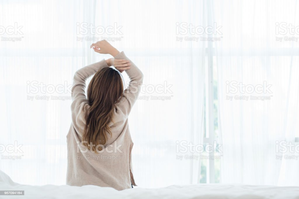 Back view of happy beautiful young Asian woman waking up in morning, sitting on bed, stretching in cozy bedroom, looking through window. Funny woman after wake up. She is stretching and smiling. stock photo